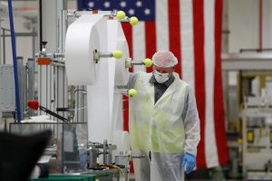 factory working in front of american flag