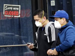 closed sign behind people wearing masks