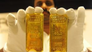 man holding two gold bars
