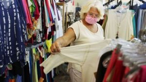 woman wearing mask looking at clothes
