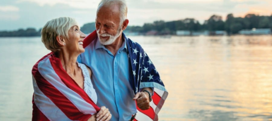 Retired couple walks along a lake wearing an American flag
